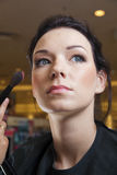 Young woman and make-up brush Stock Photos