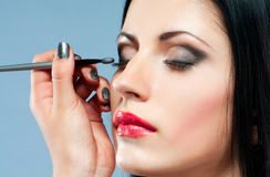 Young woman with make-up brush Stock Images