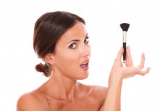 Young woman with make up brush looking at camera Stock Photos
