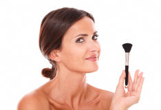 Young woman with make up brush showing her purity Stock Image