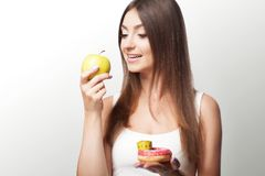 A young woman makes a choice between healthy and harmful food. S. Port. Diet. The concept of health and beauty. On a gray background Stock Photos