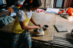 Young woman makes cosmetic paste from ground bark in a small village near Bagan. Young woman makes cosmetic paste from ground bark, popular with men and women Stock Images