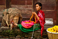 A young woman makes flower garlands in Kathmandu, Nepal Stock Photo