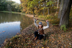 Young woman makes fun with a wood stick in a forest by autumn Royalty Free Stock Images