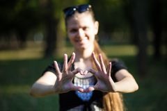 Young woman makes hands in shape of love heart royalty free stock photography