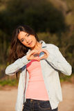 Young woman makes heart shape with hands Royalty Free Stock Photography