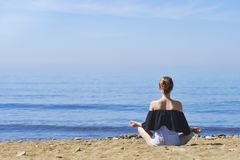 Young woman makes meditation in lotus pose on sea / ocean beach, harmony and contemplation. Beautiful girl practicing yoga at sea Stock Photo
