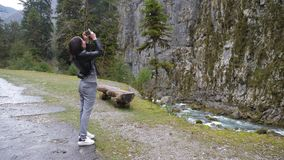 Young woman makes photo of mountain river landscape on smartphone camera, to share on internet social media through. Photo application for mobile device stock footage