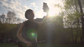 Young woman makes self-portrait on the phone next to the bike on a summer day stock footage