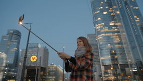 Young woman makes selfie at the background of night modern city center. Young Woman in a coat is Smiling and Taking Selfie at the Background of Buildings in stock video