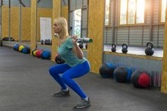 Young woman makes a squats holding a barbell without weight on t stock images