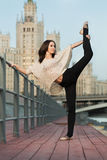 Young woman makes a stretching leaning on railing Stock Photos
