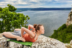 Young woman makes yoga pose on the rock above beautiful big river. Stock Photography