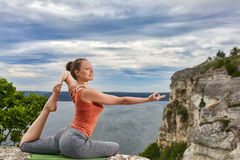 Young woman makes yoga pose on the rock above beautiful big river. Royalty Free Stock Images