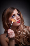 Young woman with the makeup brush Stock Photography