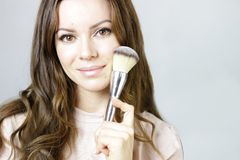 Young Woman with Makeup Brush. Pretty young woman holding a makeup brush. Beauty headshot with makeup brush Stock Photos
