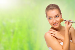 Young woman with makeup brush on spring background Stock Photography