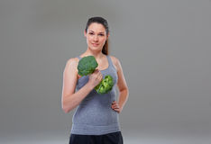 Young woman making arm exercise with broccoli, symbol Stock Photo