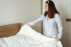 Young woman making bed Royalty Free Stock Photo