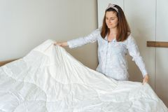 Young woman making bed Stock Photography