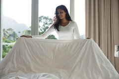 Young woman making bed Stock Image