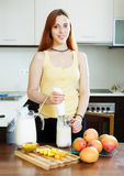Young woman making beverages with blender from mango Stock Images