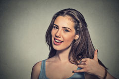 Young woman making a call me sign and smiling Stock Photos