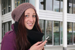 Young woman making a call with a smartphone or mobile phone outd. Young woman in winter making a call with a smartphone or mobile phone outdoor in town Royalty Free Stock Photos
