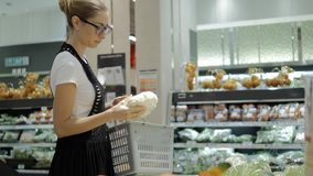 Young woman making choice in grocery store with fruits.