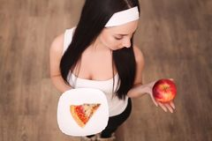 Young woman making choice between healthy and harmful food.  Royalty Free Stock Image
