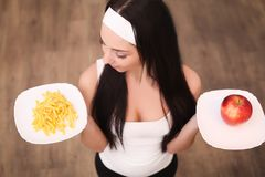 Young woman making choice between healthy and harmful food.  Stock Images