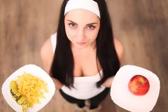 Young woman making choice between healthy and harmful food Royalty Free Stock Photo