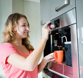 Young woman making coffee cup machine kitchen interior Royalty Free Stock Photos