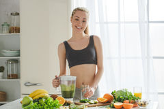 Young woman making detox smoothie at home Royalty Free Stock Photos