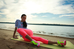 Young woman making fitness exercises on sand beach Royalty Free Stock Photo