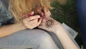 Young woman making floral mehendi on a hand using henna. stock video footage
