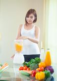 Young Woman Making Fruit Smoothie in Blender Stock Images