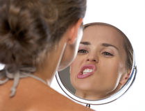 Young woman making funny faces while looking in mirror. Isolated on white Royalty Free Stock Photos