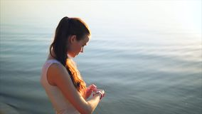 Young woman making gestures on a wearable smart watch computer device. Female using smartwatch outdoor near the sea during sunset stock video footage