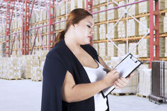 Young woman making goods list in warehouse. Young woman making goods list on her clipboard while standing in warehouse Royalty Free Stock Photography