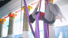 Young woman making gymnastic elements on aerial silk. Slow motion stock video