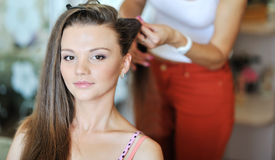 Young woman making hairstyle by stylist artist Stock Photos