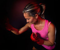 Young woman making a hard punch during training Royalty Free Stock Photos