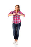 Young woman making a heart hand gesture Stock Photos