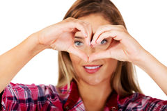 Young woman making a heart hand gesture Stock Images