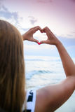 Young woman making heart shape Stock Images