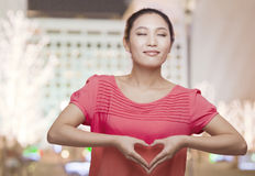 Young Woman Making Heart Sign with Hands Stock Photo