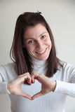 Young woman making heart sign with hands. Happy young woman making heart sign with hands isolated on grey Royalty Free Stock Photography