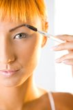 Young woman making her makeup. She's looking at camera. Closeup on face. Front view Stock Image