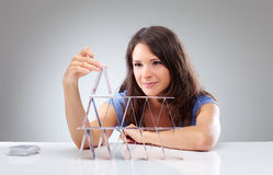 Young woman is making a house of cards 2 Royalty Free Stock Photo